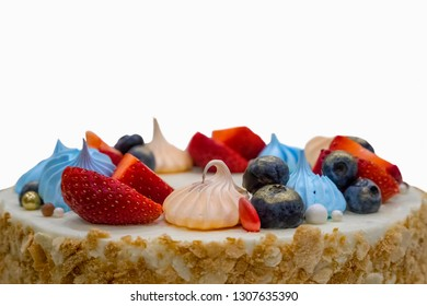Isolated birhtday cake decorated with marshmallow, strawberries and blueberries