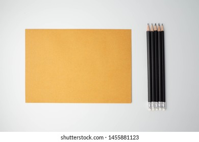 Isolated black pencill beside brown paper (note, document, notation, letter, mail, file or monograph) on white background for background.