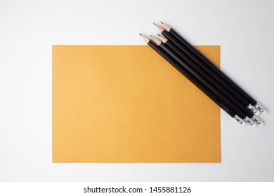 Isolated black pencill on brown paper (note, document, notation, letter, mail, file or monograph) on white background for background.