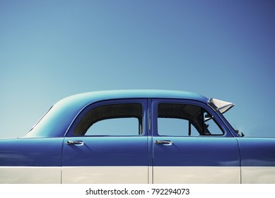 Isolated blue and white vintage retro antique car with bright happy blue sky behind it for travel vibes.