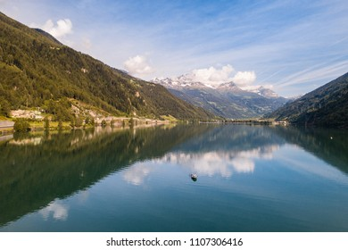 Isolated boat on the alpine lake, lake of Poschiavo in the Canton Grisons, Switzerland