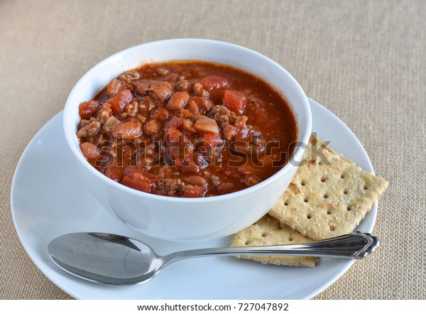 Isolated bowl of chili soup with spoon and whole wheat saltine crackers.  Beans, beef, tomatoes, and spices as main ingredients.
