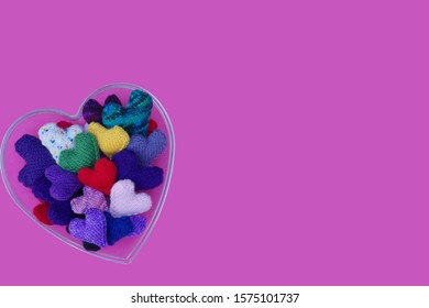 Isolated Bowl Filled With Knitted Hearts In Different Colors Against A Pinkish Purple Background - Seen From Above