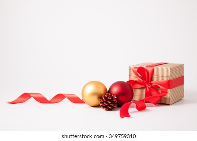 Isolated brown cardboard box, bow and ribbon with christmas decoration on white background
