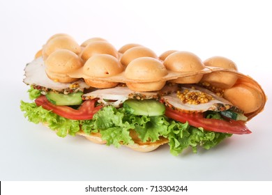 Isolated bubble waffle with ham, meat, cheese, tomato, salad, cucumber and mustard on the white background.
