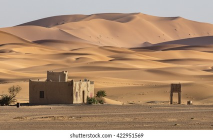 Isolated building with sand dunes of Erg Chebby near Merzouga, Morocco