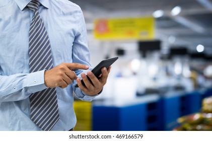 isolated business man hold the smartphone on shopping mall background