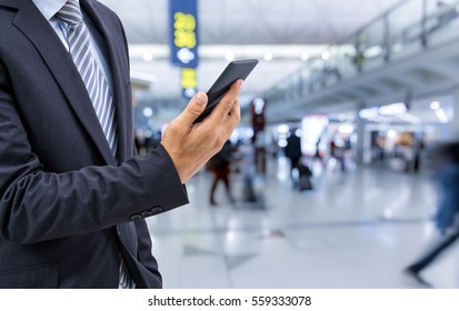 isolated business man hold the smartphone on airport background