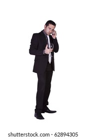 Isolated businessman celebrating with a glass of drink while talking on the phone