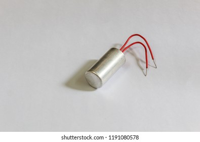 Isolated capacitor with positve and negative nodes on white background.with selective focus on the subject.low light photography.