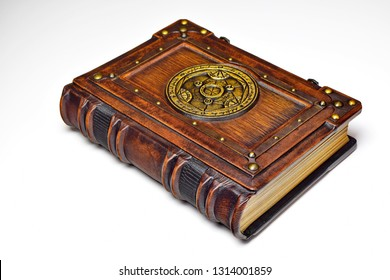 Isolated, captured from the left side, vintage book with the gilded symbol. The transmutation circle symbol is attributed to a German alchemist from the 17th century.