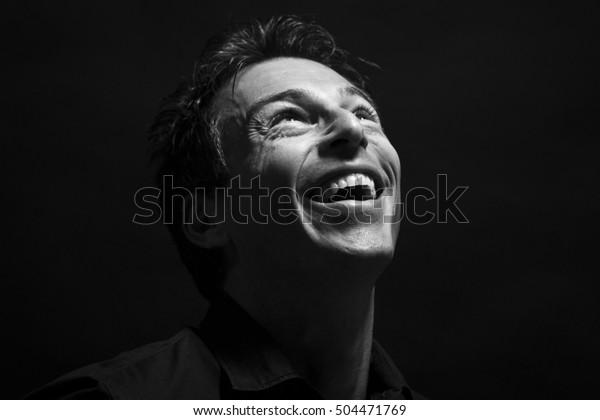 Un homme caucasien isolé se voit rire . Arrière-plan noir, image noire et blanche
