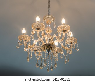 isolated chandelier hanging from a white ceiling