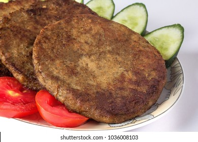 Isolated Chapli Kabab dish with vegetable salad, Indian or pakistani barbecue food.