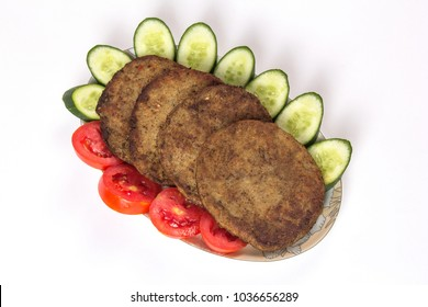 Isolated Chapli kabab dish with vegetable salad on white background, Indian or pakistani food decoration of Tomatoes and cucumbers in plate.