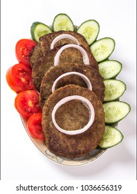 Isolated Chapli kabab dish with vegetable salad on white background, Indian or pakistani food decoration of Tomatoes and cucumbers in plate, Spicy ramadan meal.