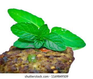 Isolated Chapli kabab with fresh peppermint leaves