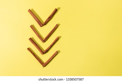 Isolated cinnamon sticks sorted into a shape of an arrow - overhead shot on a bright yellow background