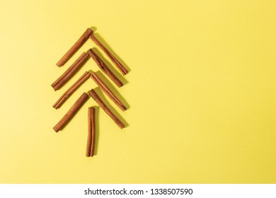 Isolated cinnamon sticks sorted into a shape of a tree - overhead shot on a bright yellow background