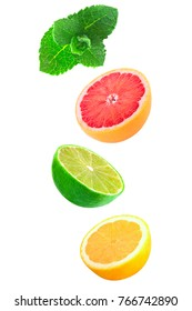 Isolated citrus fruits. Falling pieces of mint, lemon and lime isolated on white background with clipping path