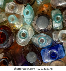 Isolated, close up overhead perspective of old clear and colored glass bottles and jars against a neutral background