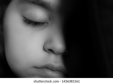 Isolated close up portrait in black and white of a young beautiful girl sleeping