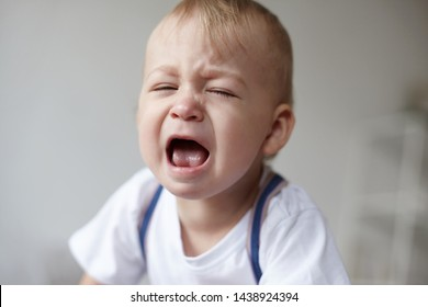 Isolated close up portrait of tired baby crying out loud, feeling sleepy or being hungry, opening mouth, screaming. Unhappy stressed infant having painful facial expression because of teething