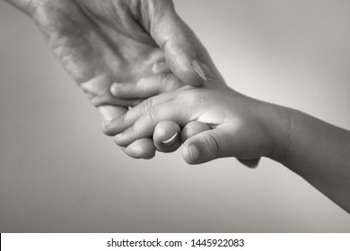 Isolated closeup of mother holding small child's hand,