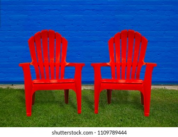 Isolated closeup of two vibrant red Adirondack chairs, turned slightly together and facing the camera. Seats sit empty on bright green grass against a royal blue brick wall background.
