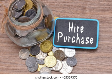 Isolated coins in jar with Hire Purchase word on mini chalkboard - financial concept