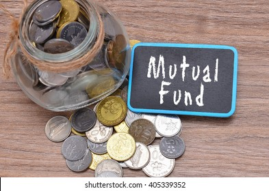 Isolated coins in jar with Mutual Fund word on mini chalkboard - financial concept