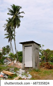 Isolated communal toilet building next to some coconut palms in small village in Asia