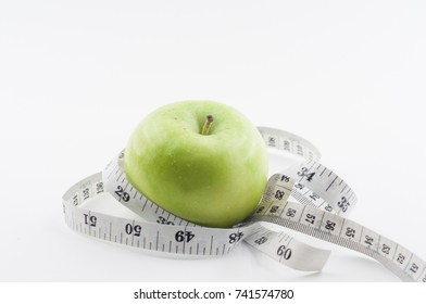 The isolated conceptual of Apple with measuring tape for weight loss concept.