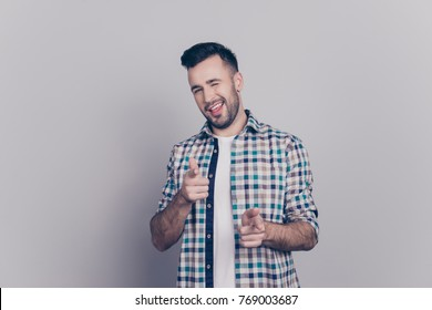 Isolated confident, smiling man in checkered shirt pointing towards his forefingers and winking with one eye to camera over grey background