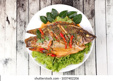 Isolated of Curry-fried Tilapia fish with spicy topping on white dish.