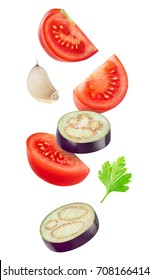 Isolated cut vegetables. Raw slices of eggplant, tomato and garlic flying in the air isolated on white background with clipping path