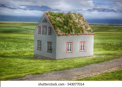 Isolated cute icelandic house with a turf roof in the middle of the valley near the Glaumbaer turf farm in Skagafjordur, Iceland, where a mountain range can bee seen on the background