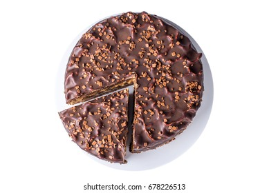 isolated delicious chocolate layered cake with nougat and sponge cake in the cut on the plate, top view