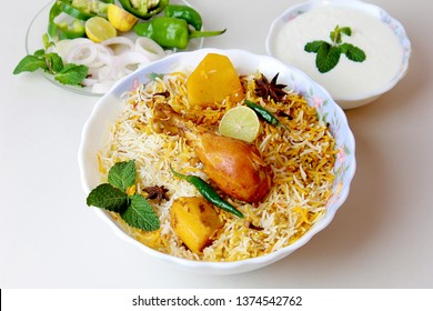 Isolated delicious spicy chicken biryani with raita in white bowl on white background, Indian or Pakistani ramzan food. Beautiful view of traditional spicy indian food, Iftar meal, Ramadan dinner.