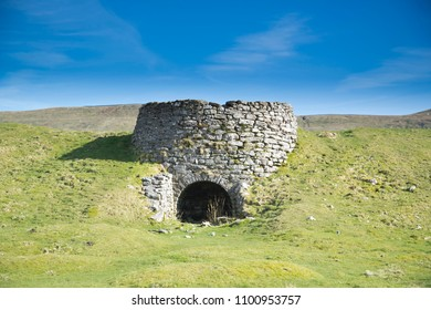 Isolated derelict Historic industrial Lime Kiln near the village of Thornton in Lonsdale in the North Yorkshire Dales in England UK with moorland grass in sunny weather with blue skies and clouds