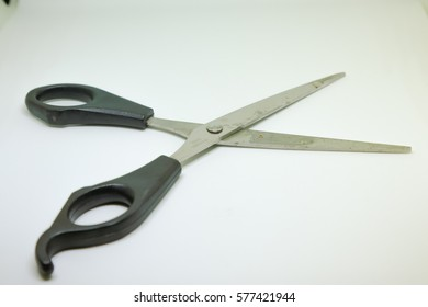 isolated disclosed scissors with black handle on a light background