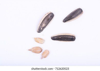Isolated dried black Sunflower seeds scattered on white background.
