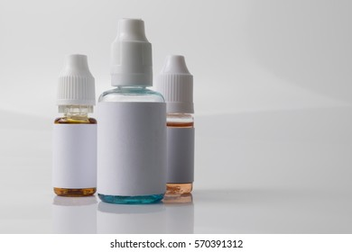 Isolated e liquid bottles for vaping devices on a white background with reflection.