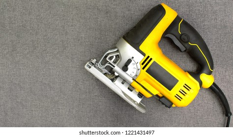 Isolated electric jig saw on a grey texture background