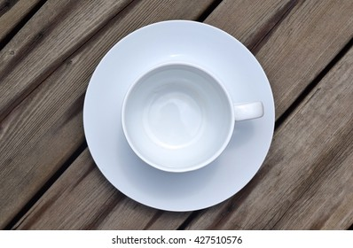 An isolated empty coffee cup on a wood deck.