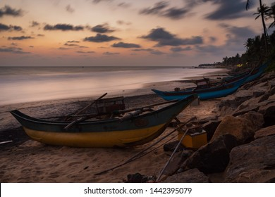 Isolated and empty fisherman boat from Sri Lanka. Boat on the tropical beach with sea and island on the back at sunset with epic and dramatic sky.