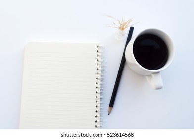 isolated empty notebook pencil and white cup coffee on white background. soft focus