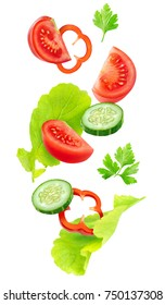 Isolated falling vegetables. Slices of tomato, cucumber, red bell pepper and lettuce leaves (fresh salad ingredients) in the air isolated on white background with clipping path