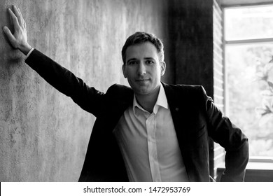 isolated fashion business man posing against black backgroung wall. wearing style  suite, white shirt , blazer and trousers. handsome businessman believe in success
