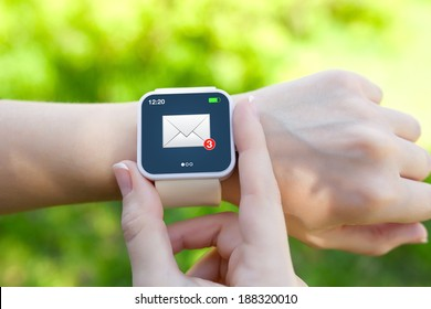 Isolated female hands with white smartwatch with email on the screen on a background of green grass